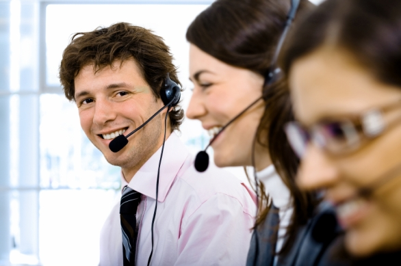 Customer service team working in headsets. Focus placed on smiling man in back.